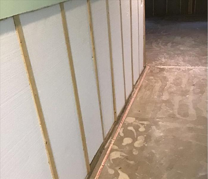 Drywall removed from a basement wall with studs showing.