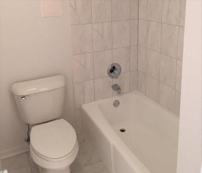 New white bathtub and toilet in a bathroom.