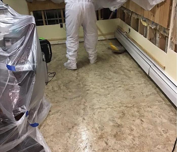 Muddy tile floor with a SERVPRO worker in a white suit with a mop.