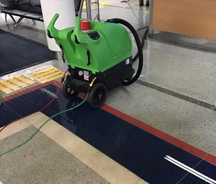 A green water extractor on a tile floor of an office lobby.