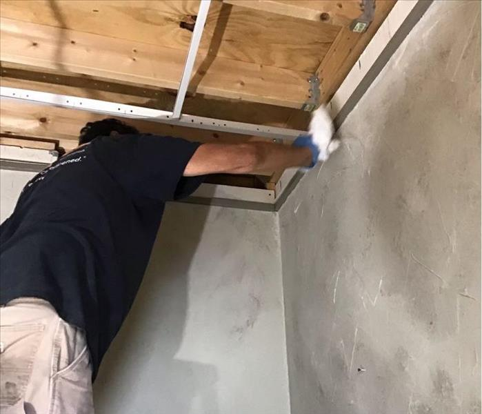 SERVPRO employee cleaning soot off of a wall.