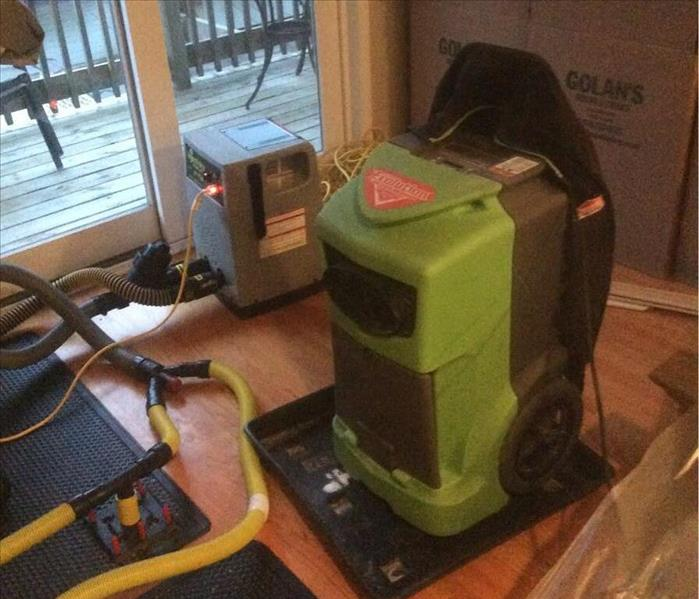 Green SERVPRO equipment drying out hardwood floors with yellow hoses on the floor.
