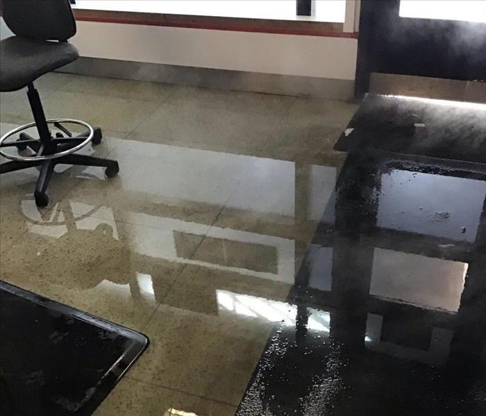 Wet tile floor of an office hallway with a chair in the background.